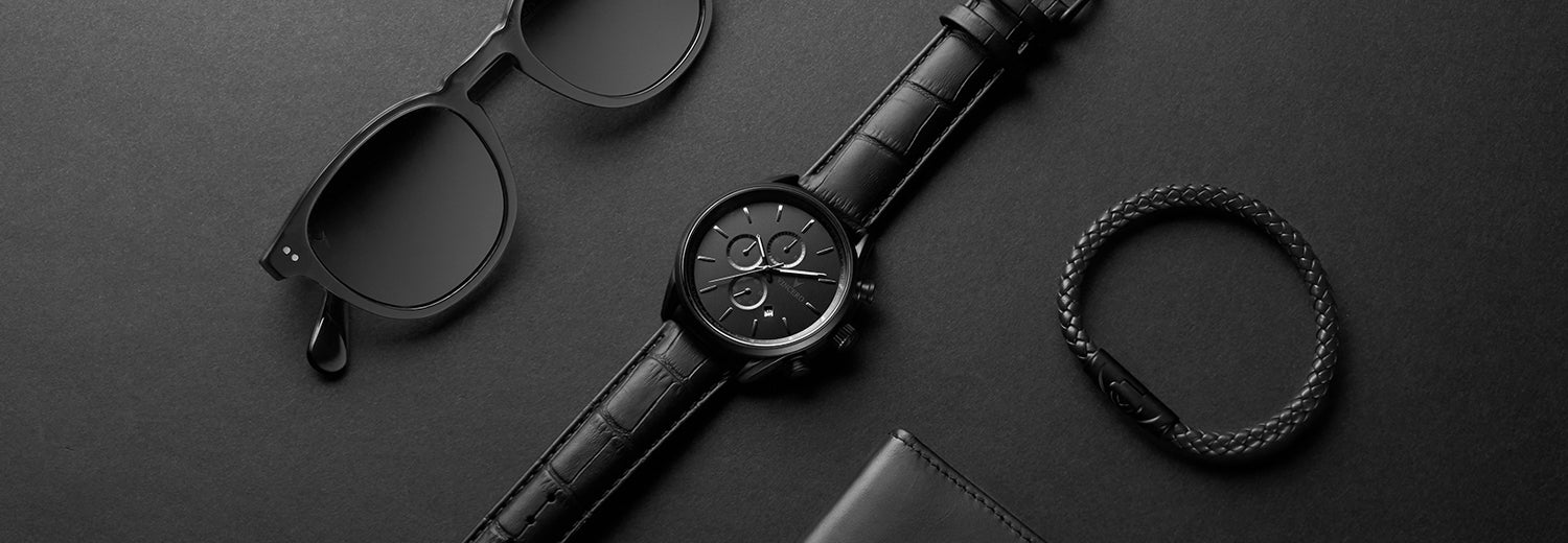 Black sunglasses, watch, and bracelet in matte black background