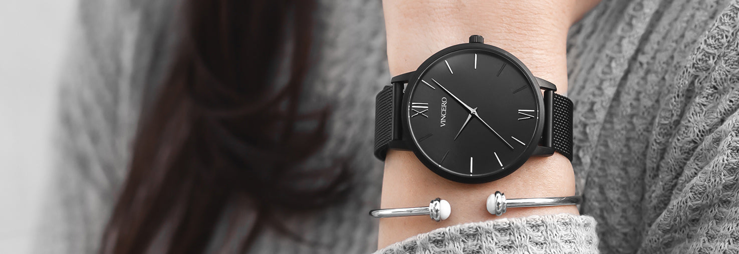Woman in grey sweatshirt with matte black watch and silver cuff bracelet