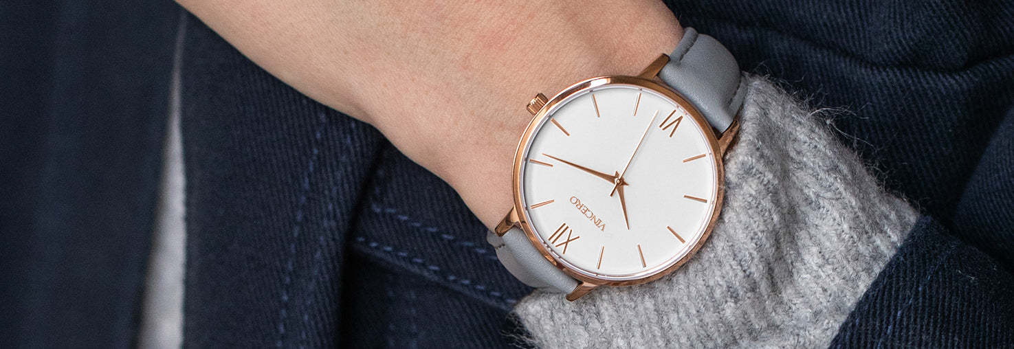 Close up of white and rose gold watch with grey leather strap