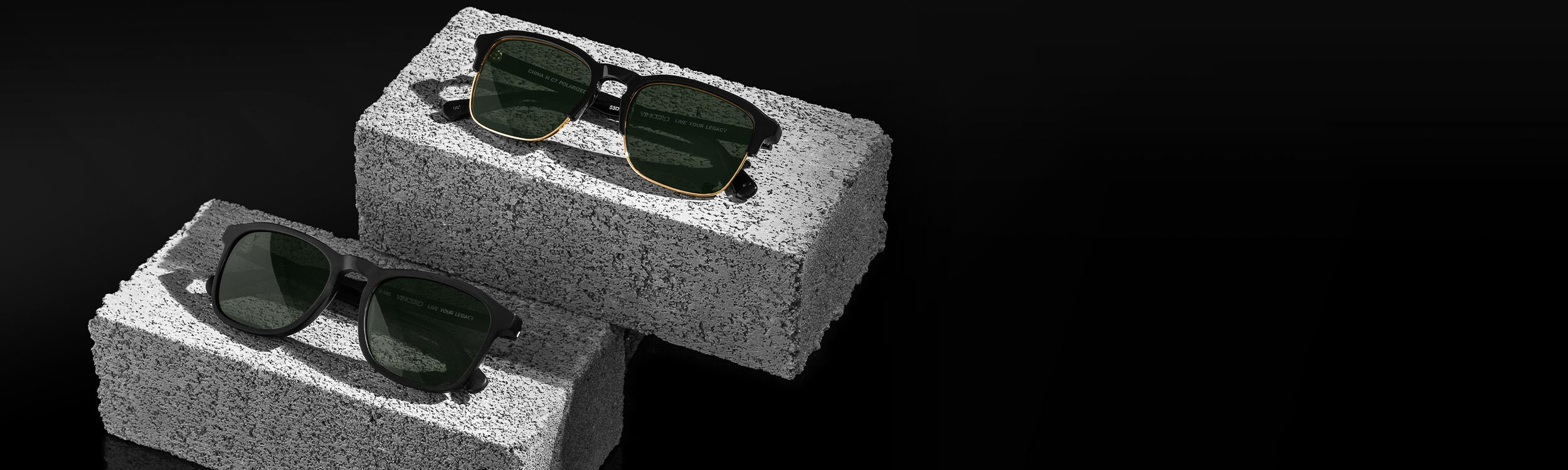 Two sunglasses laying on bricks with black background