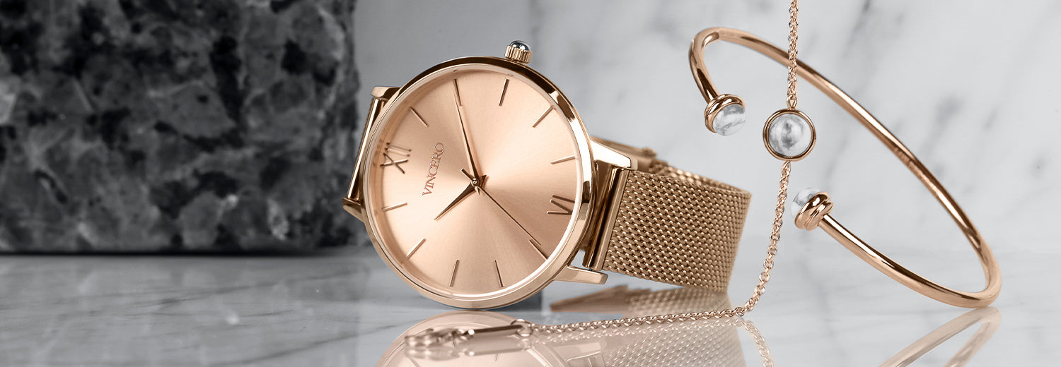 Rose gold watch with mesh strap with rose gold bracelet and cuff in white marble background