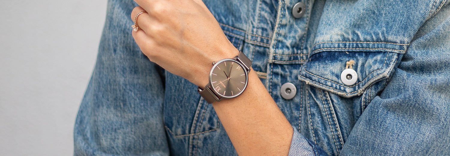 Woman in denim jacket wearing dark khaki watch