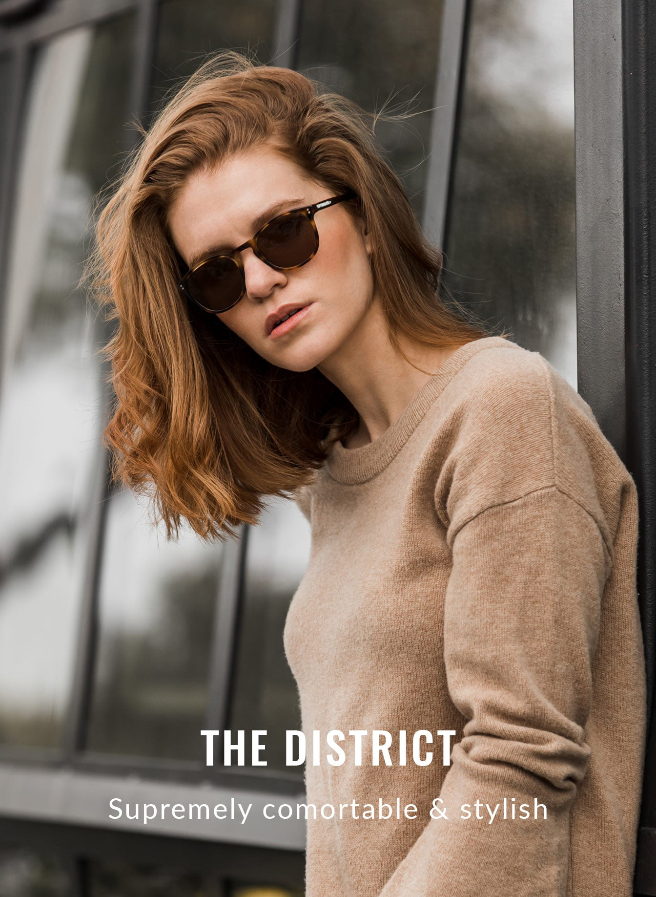 Woman in tan sweater leaning against wall in sunglasses