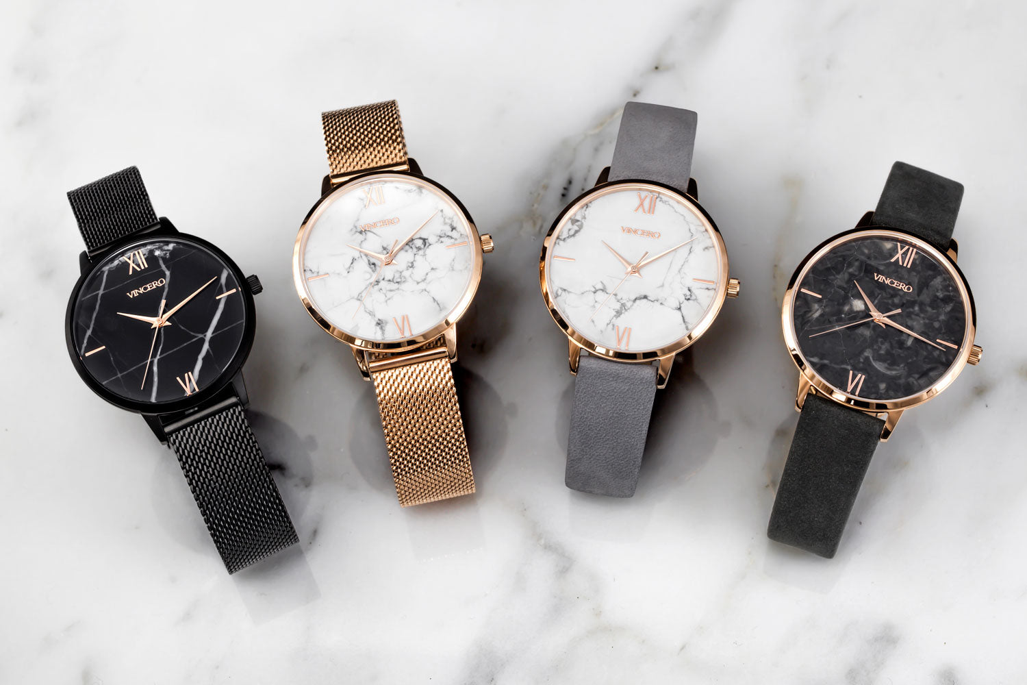 Four marble faced watches with mesh and leather straps laying in white marble