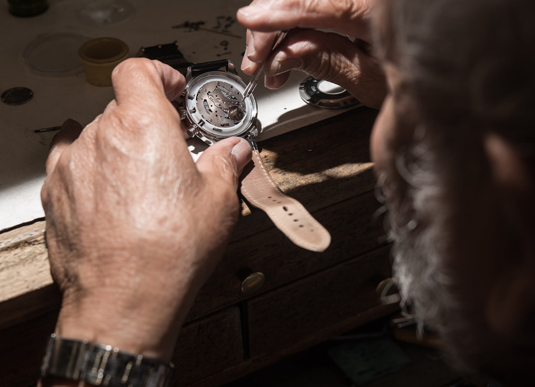 Man working with the opened back case of watch