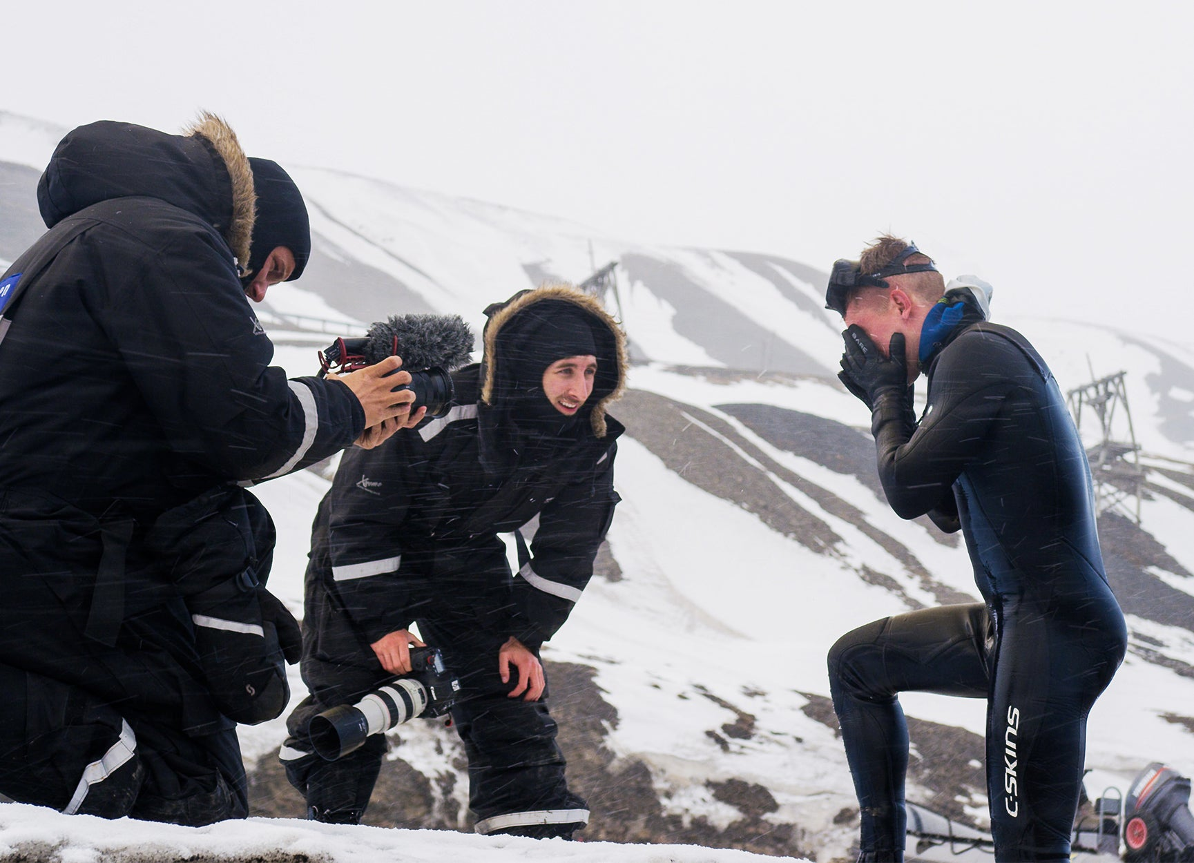 Three men in a snowy mountain doing a video shoot