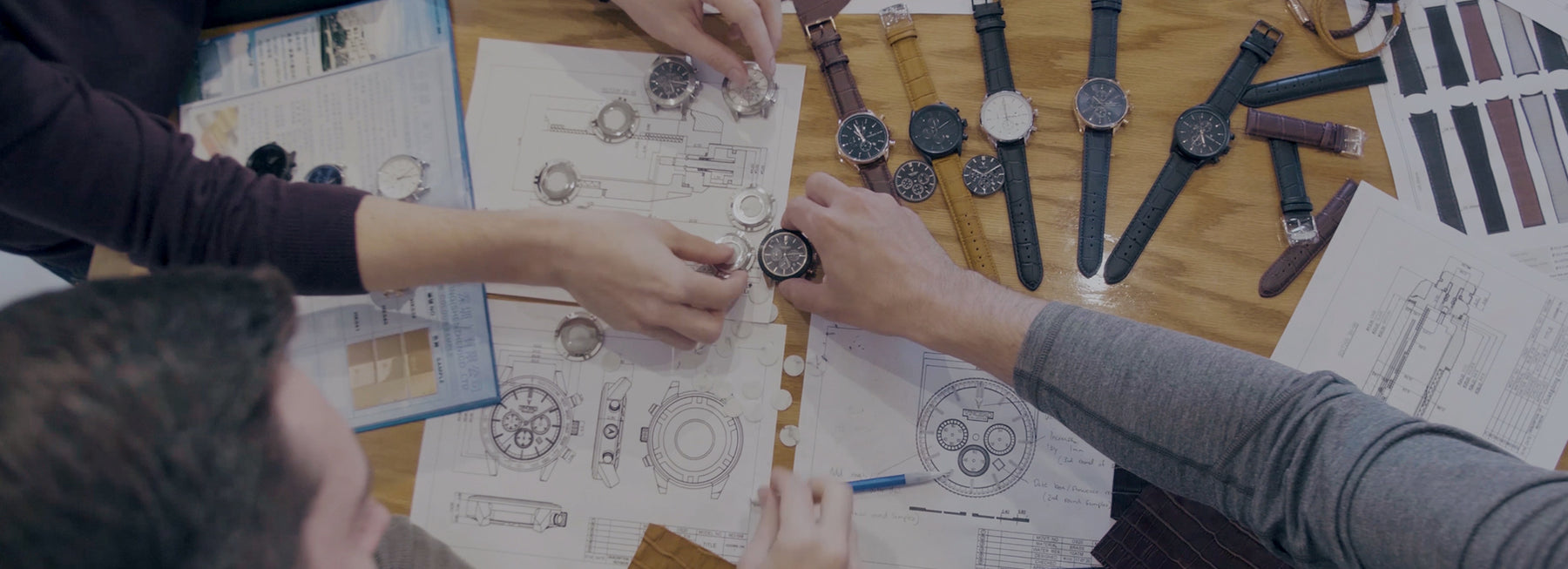 People holding unassembled parts of watch in wooden table with blueprints of watches
