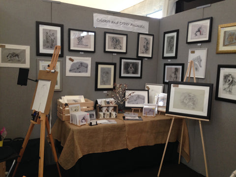 art fair stall exhibiting cricket and animal original drawings and prints with cricket mugs and cricket cards