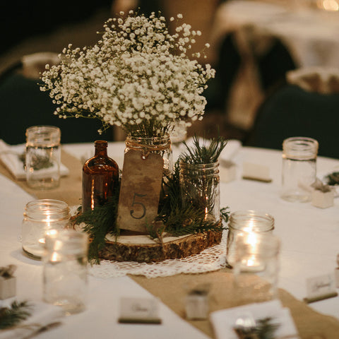 Wedding table decor with a rustic centrepiece featuring mason jars and baby's breath and mason jars as drinking glasses