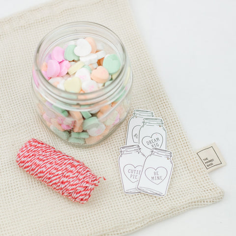 decorative red twine and valentines gift tags next to a wide mouth mason jar filled with valentine's candy
