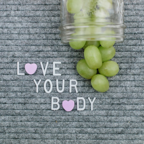 grey letter board that says love your body with a fruity mason jar pint full of green grapes