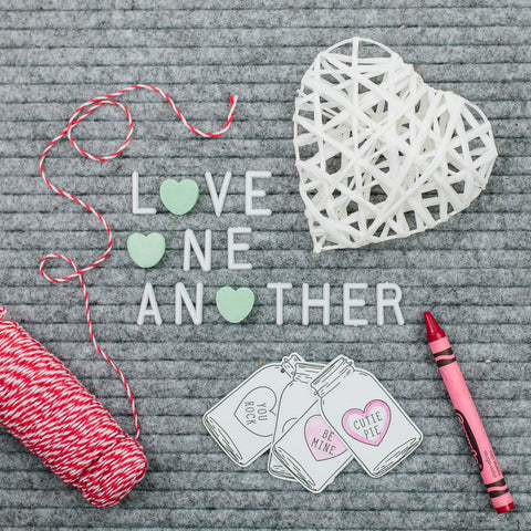 grey letter board that says love one another with valentine's day printable gift tags and red twine