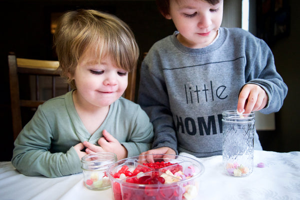two young boys filling mason jars with their favorite valentine's candies