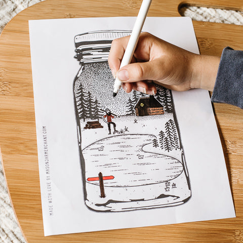 child's hand holding felt pen coloring a free printabe coloring page featuring a lumberjack and a cabin by a lake