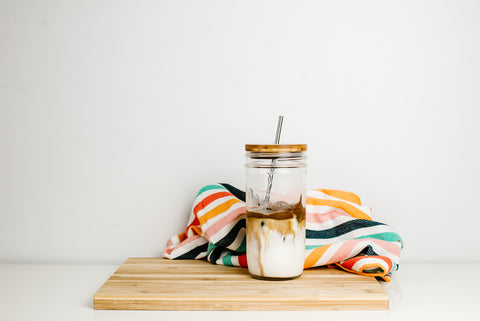 whipped coffee in a 24 oz mason jar with a sustainable bamboo lid and stainless steel reusable straw