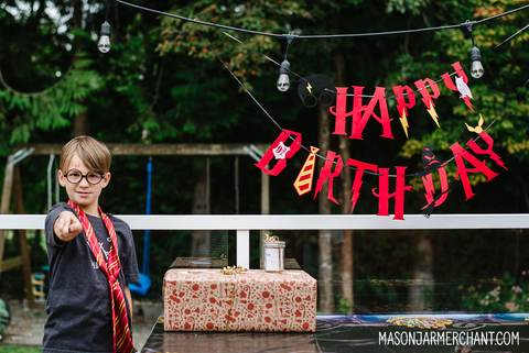 young boy standing next to a red felt Happy Birthday sign and wearing Harry Potter glasses and a Gryffindor Hogwart's tie and pointing a wooden wand