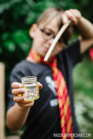 Boy wearing Harry Potter glasses and a red and yellow tie pointing a wooden wand at a tiny mason jar filled with yellow liquid