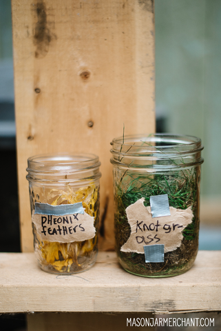 mason jars on a DIY pallet shelf filled with flowers and grass for a DIY potion shop at a Harry Potter themed birthday party