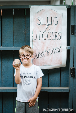 Young boy wearing Harry Potter glasses and holding a mason jar labelled Basilisk Egg Shells standing in front of a handmade sign for Slug & Jiggers Apothecary