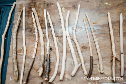 rough hand carved Harry Potter wands lined up on a sheet of plywood ready to be customized at a Harry Potter themed birthday party