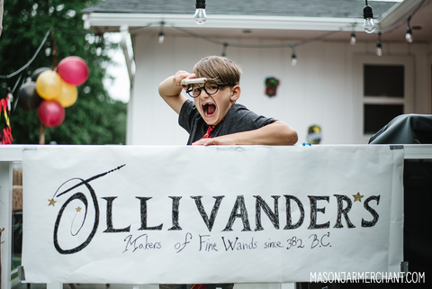 A young boy wearing Harry Potter glasses and pointing a wand and leaning over a hand painted sign for Ollivander's Wand Shop
