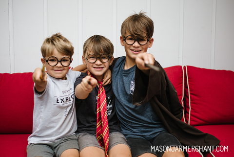 three boys sitting on a red couch wearing Harry Potter glasses and pointing wands at the camera