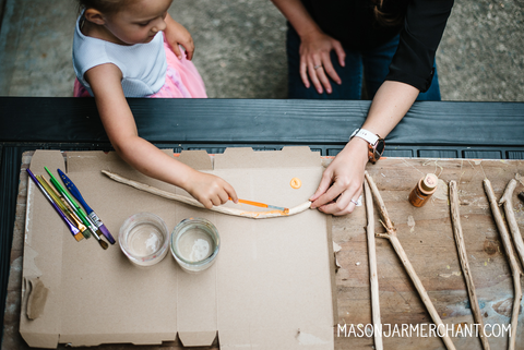 Young girl in a white and pink dress holding a paint brush and painting a hand carved wand with bright orange paint