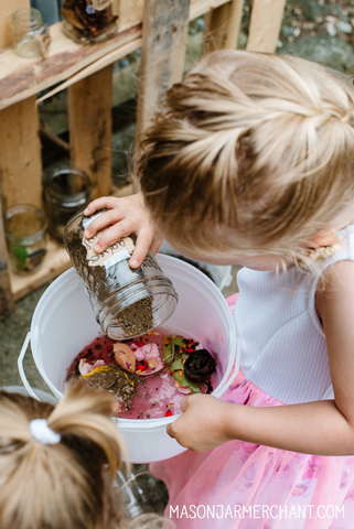 young blond girl in a pink and white dress dumping something from a mason jar into an ice cream bucket to mix up a potion
