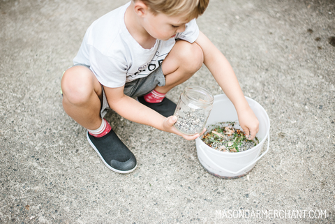 little boy wearing shorts and a tshirt and crouched next to an ice cream bucket full of leaves sticks and rocks used to make a potion