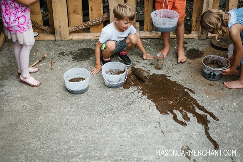 group of kids standing on concrete next to a big splash of mud