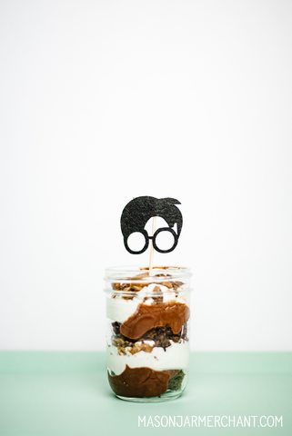 an 8-ounce regular mouth mason jar filled with layered chocolate cake, pudding and whipped cream topped with a Harry Potter silhouette cupcake topper