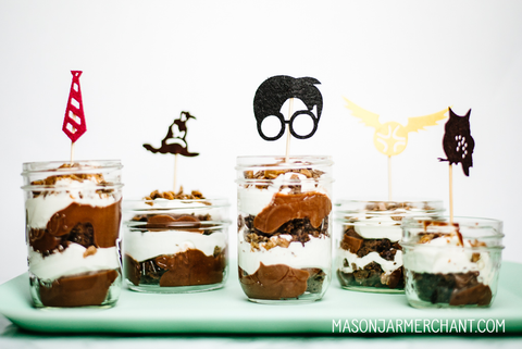 layered chocolate and whipped cream trifle in individually sized mason jars topped with felt Harry Potter cupcake toppers