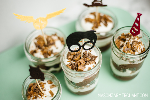 individual mason jar desserts topped with Harry Potter cupcake toppers on an aqua serving tray