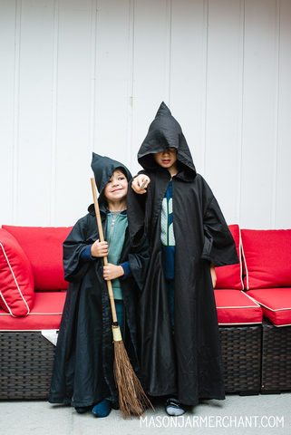 two boys wearing black wizard clocks made from thrifted flat sheets