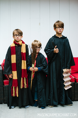 three boys dressed up as Harry Potter wearing DIY Hogwart's cloaks sewn from thrifted black flat sheets