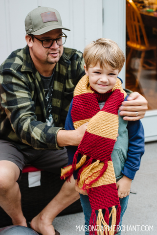 smiling boy wearing a scarlet and yellow hand crocheted Gryffindor House Hogwart's scarf