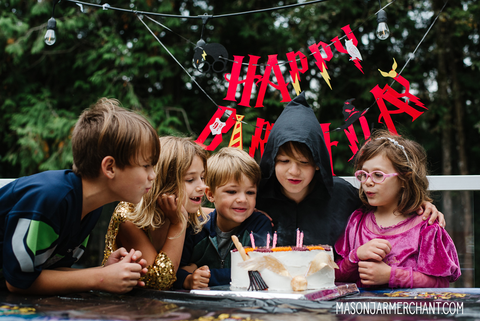 group of five kids blowing out the candles on a Harry Potter birthday cake with a red Happy Birthday banner hanging behind them