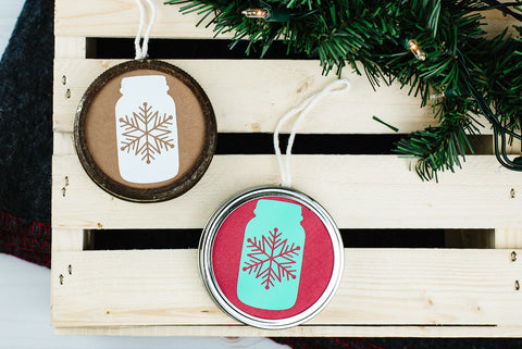 DIY mason jar ring ornaments with mason jar decals laying on a wooden crate next to an evergreen garland