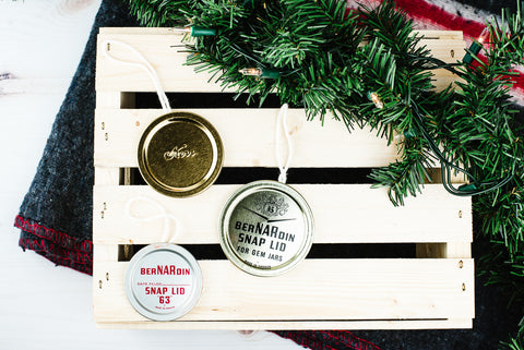 three vintage flat lid mason jar ornaments on a wooden crate