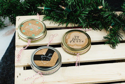 set of three handmade mason jar ornaments made from cork and stamped with holiday sayings and images