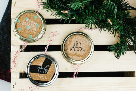 three DIY double-sided mason jar ring Christmas ornaments made from stamped cork
