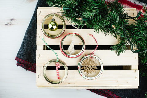 set of four DIY mason jar ring ornaments with small Christmas embellishments in the centre