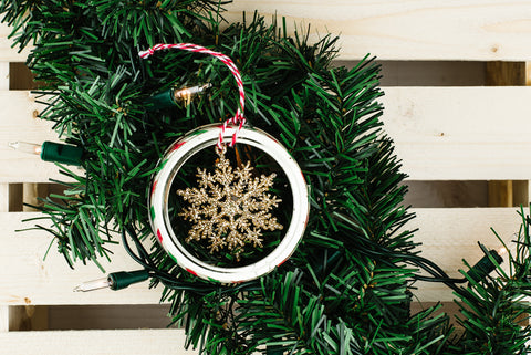 small glittery gold snowflake hanging inside a used mason jar ring with a red and white striped string
