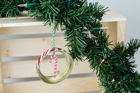 handmade mason jar ring ornament with red and white striped miniature candy cane and red and white glittery edge