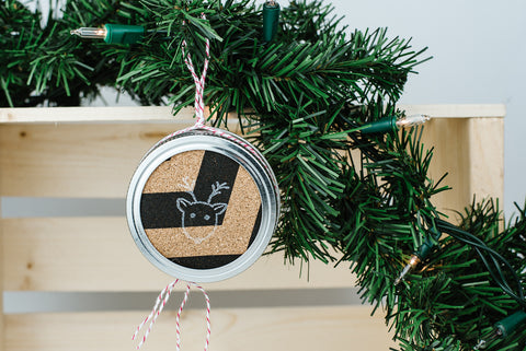 diy mason jar lid christmas ornament with black and cork chevron and a reindeer on it handing from an evergreen bough