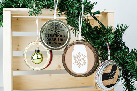 four ornaments handmade from used mason jar flat lids and rings and Christmas craft items
