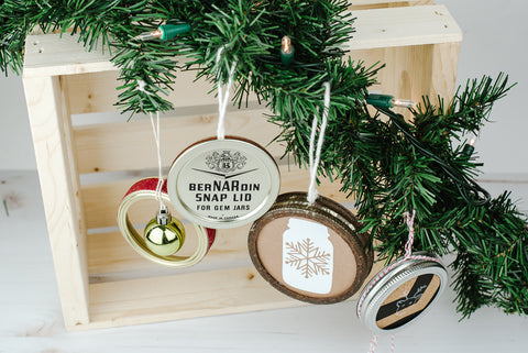 four DIY Christmas ornaments made out of used mason jar lids and rings hanging from an artificial evergreen bow in front of a natural wood crate