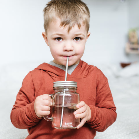 small children drinking water from a reusable glass mason jar with a stainless steel reusable straw