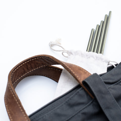 Set of stainless steel reusable straws in a drawstring pouch spilling out of a bag
