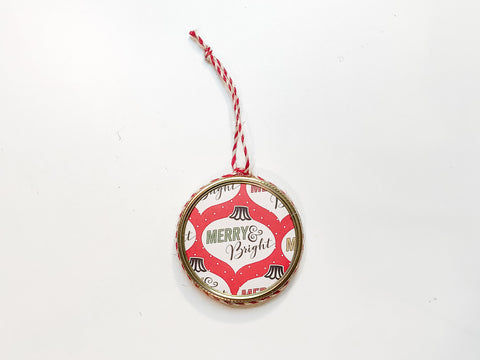 handmade mason jar ring ornament with red and white string and brightly colored scrapbooking paper that says Merry & Bright